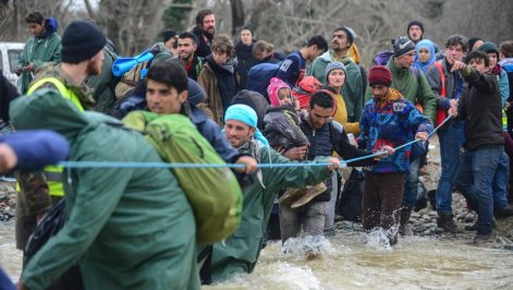 Refugees cross a river near Idomeni to enter Macedonia