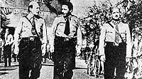 El ex presidente chileno Salvador Allende (dcha.) desfila uniformado con las milicias socialistas.
